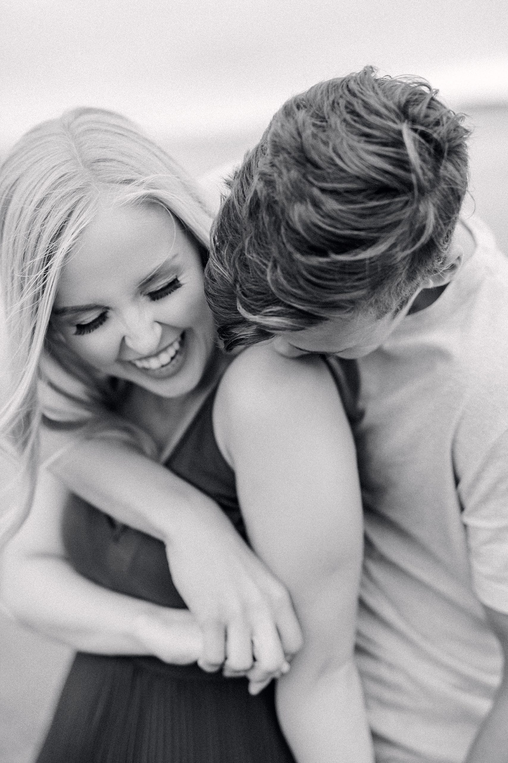 black and white image of engaged couple where the guy is kissing her shoulder