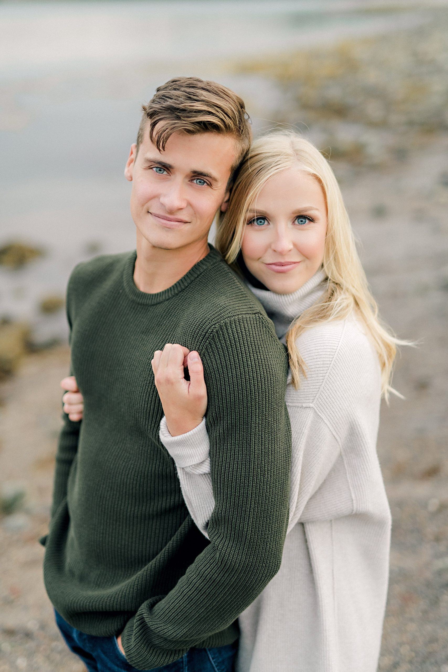 gorgeous couple wearing sweaters hugging on the beach