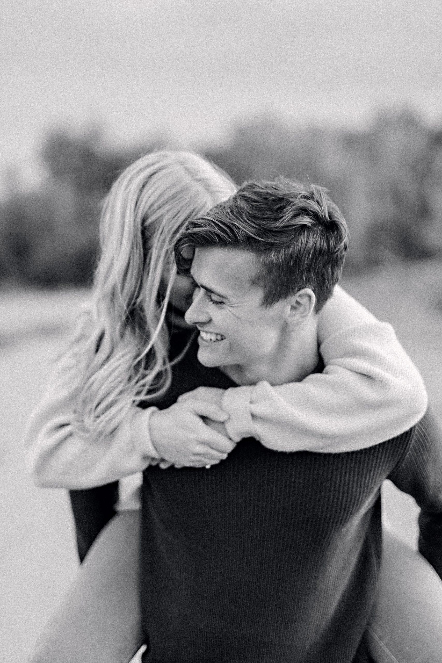 black and white image of girl on guys back