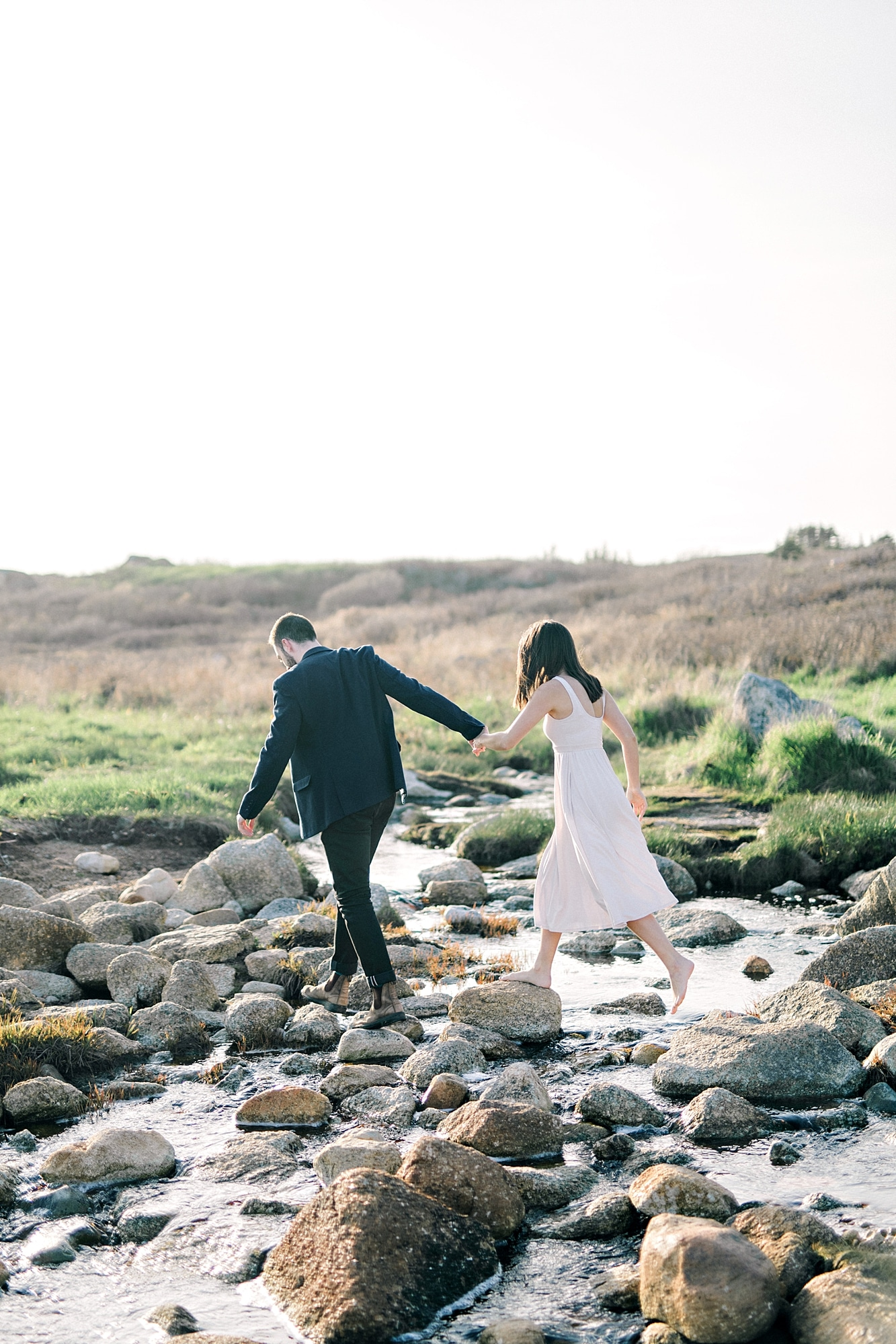Engaged couple crossing river