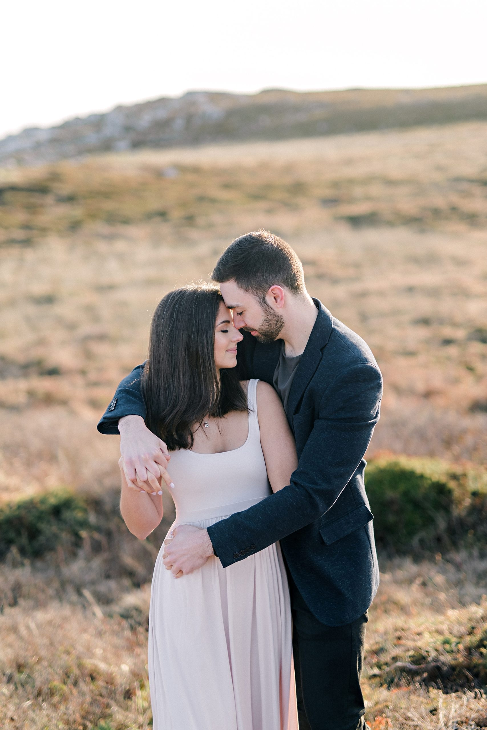 couple embracing in golden field during engagement shoot