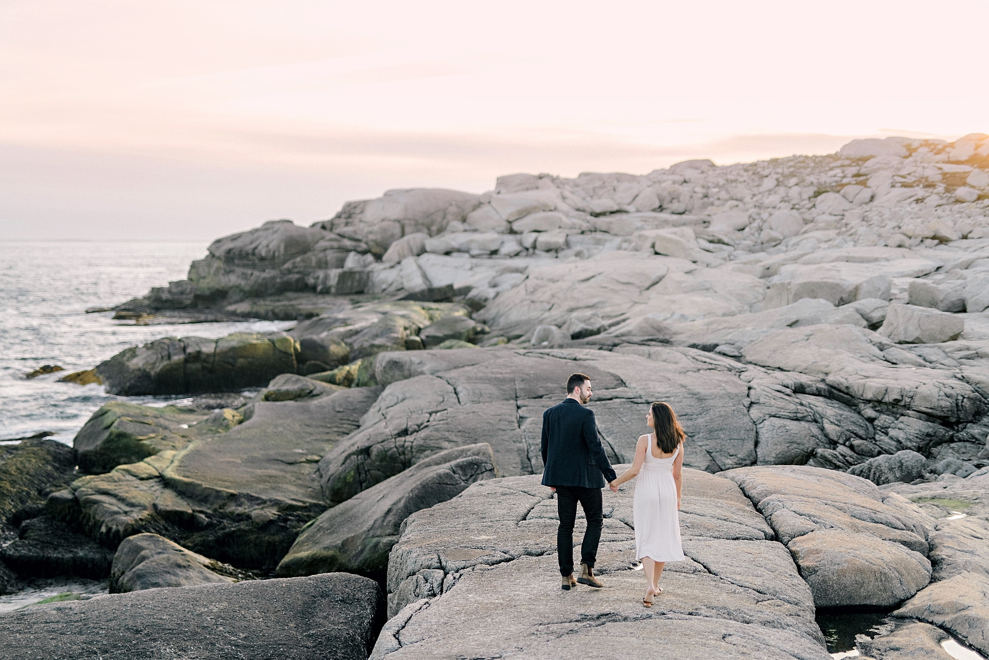 couple on grey rocks walking hand in hand into the sunset sky