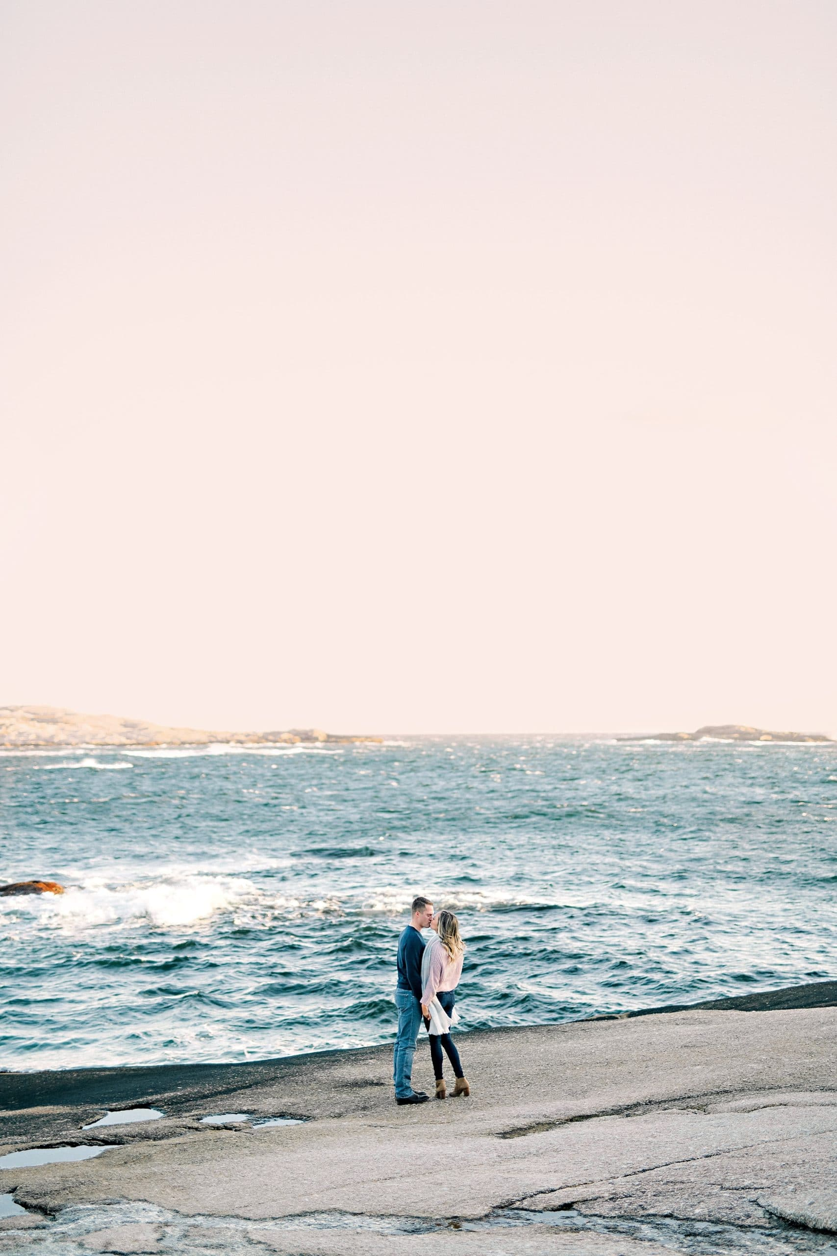 couple standing by ocean embracing