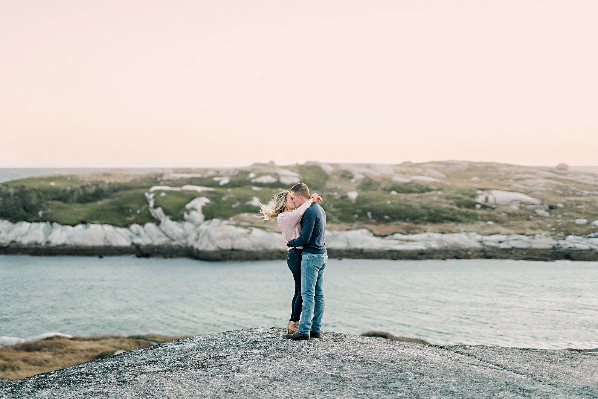 couple standing nose to nose on rocks overlooking pink sky and ocean