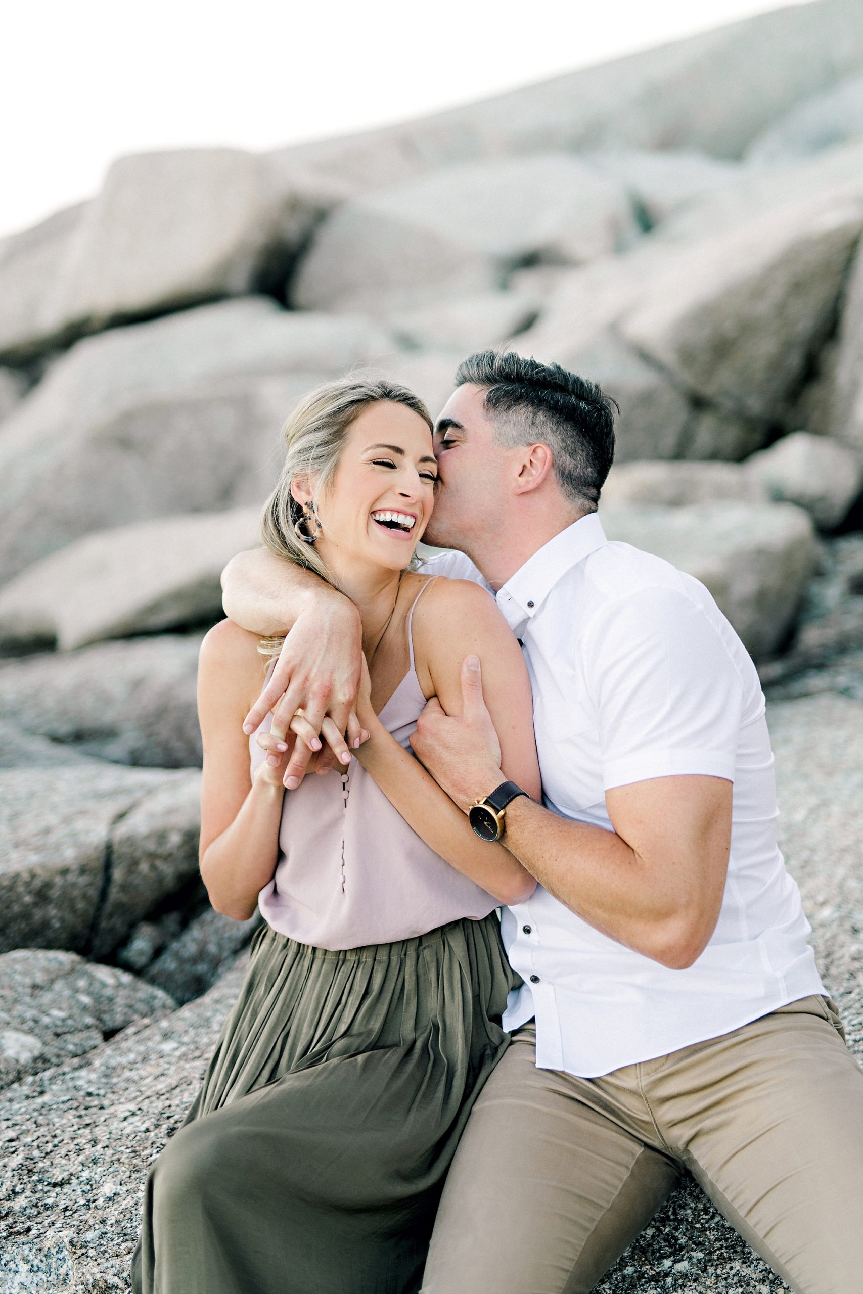 handsome guy kissing his fiancee on her cheek and making her laugh on the rocks by the ocean