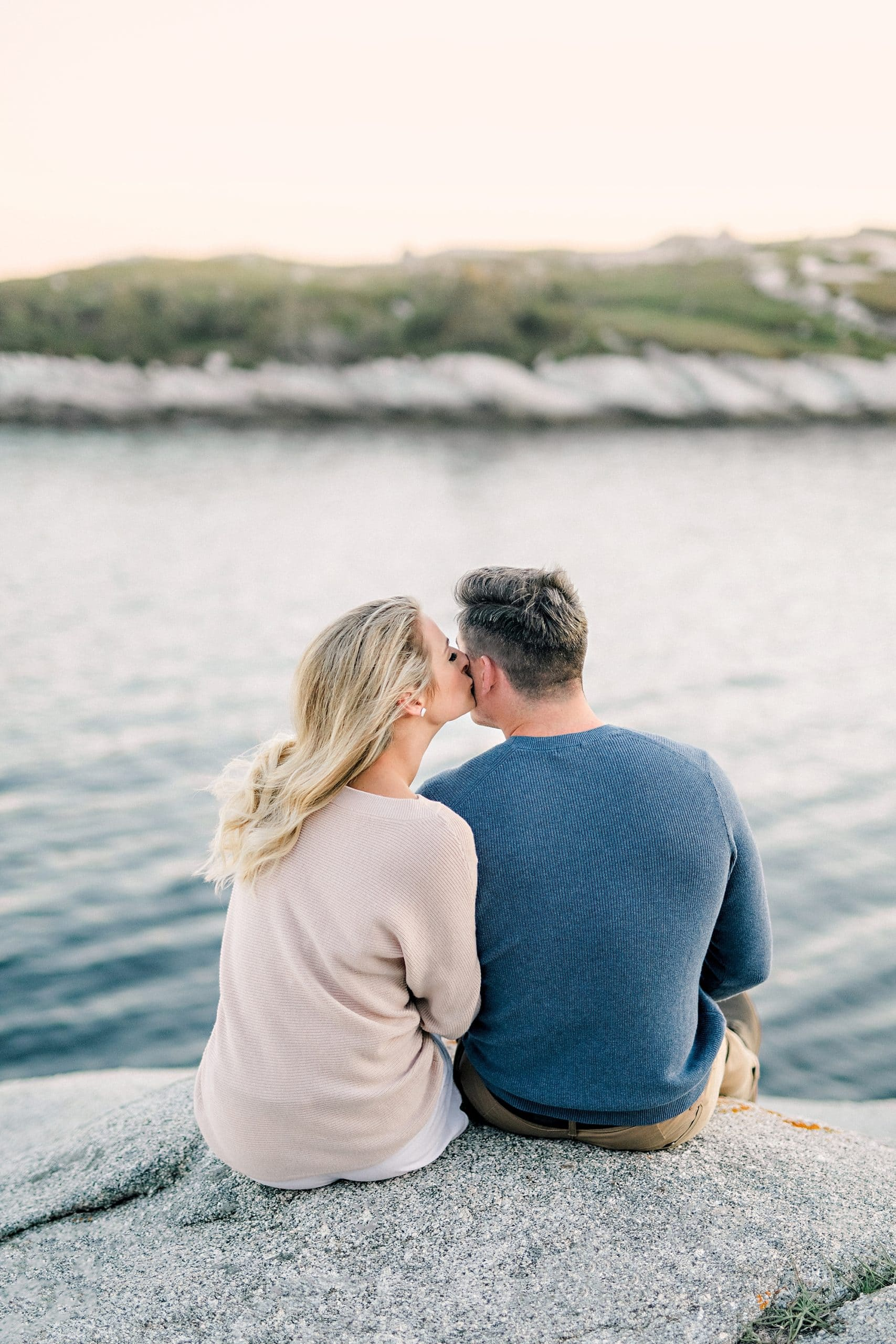 couple watching the water and sunset cozy in sweaters kissing on the cheek