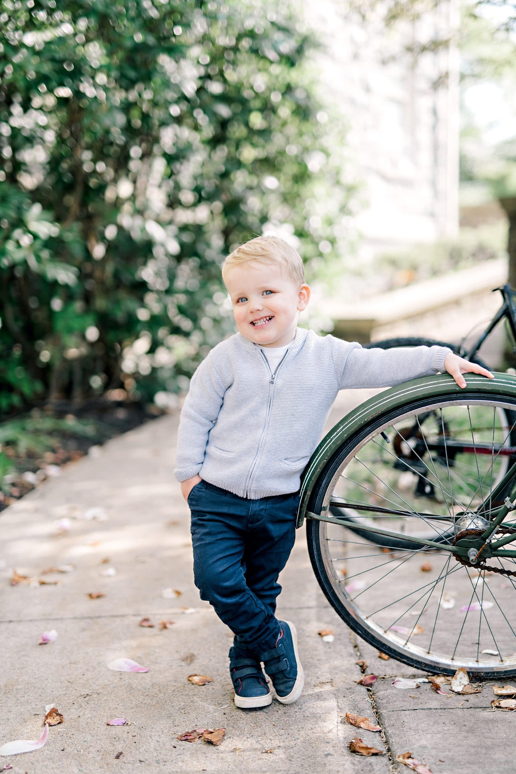 child smiling for the camera infront of a bike