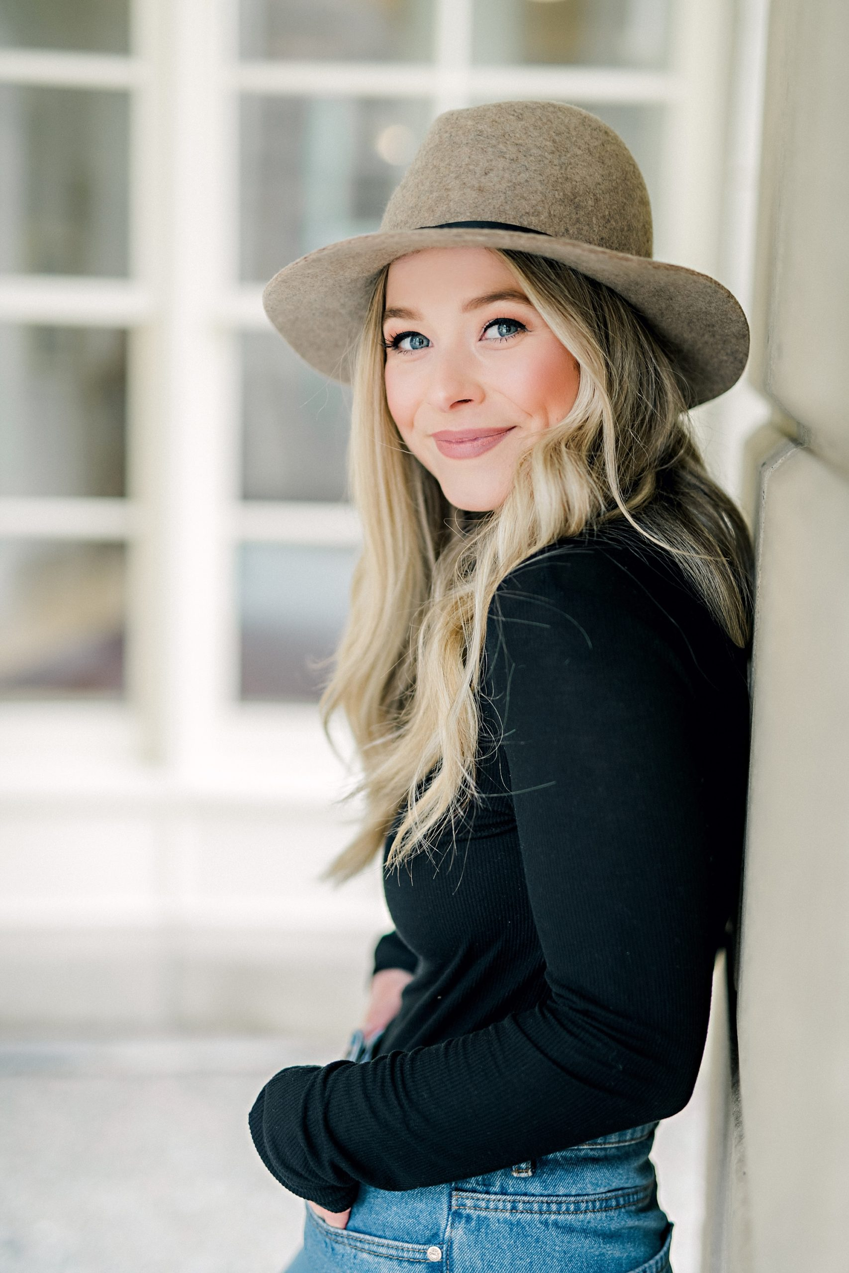 blonde girl in panama hat and black shirt smiling