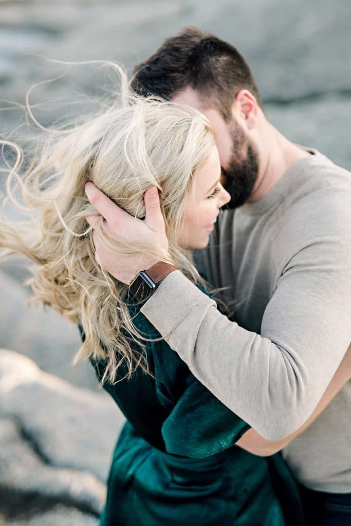 guys hands in girls blond hair as it blows in the wind