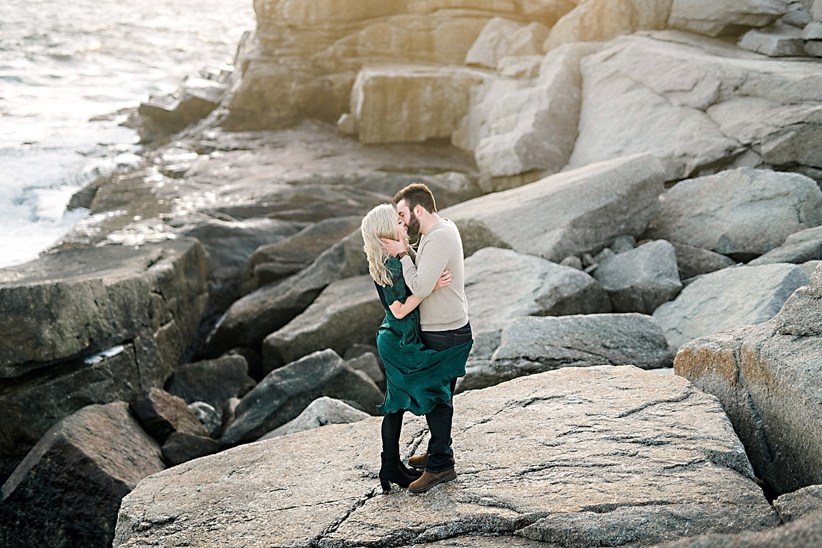 couple standing on rocky cliff in green dress