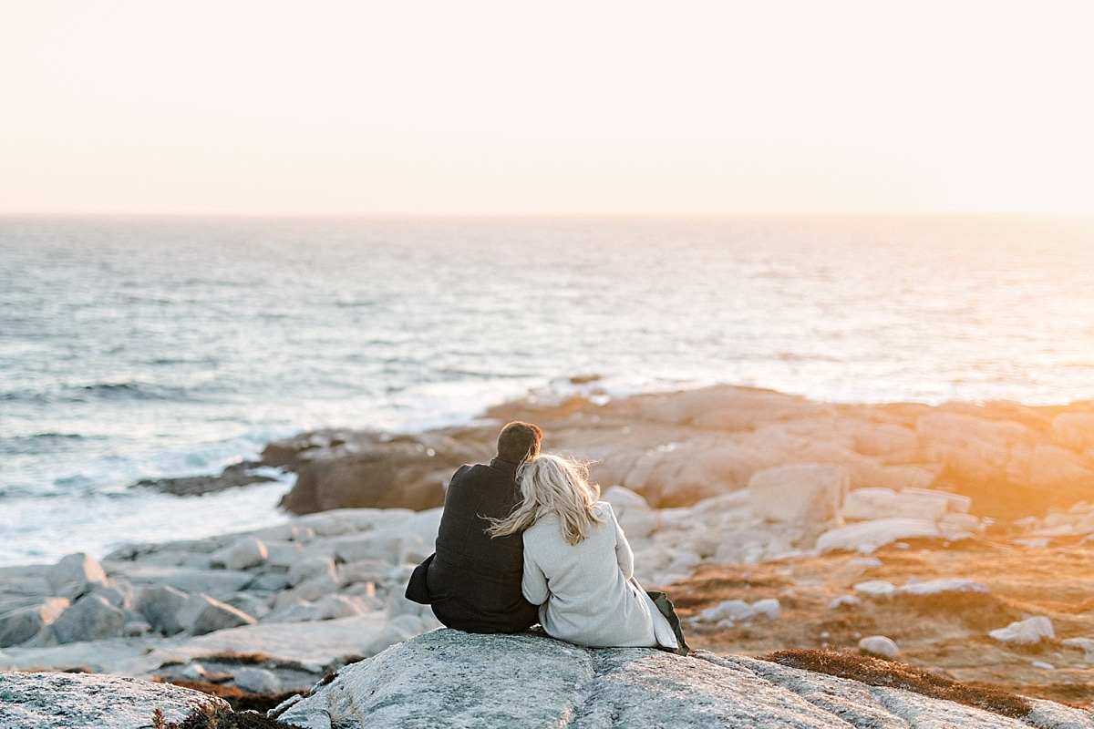 couple sitting on rocky cliffs by the ocean at sunset