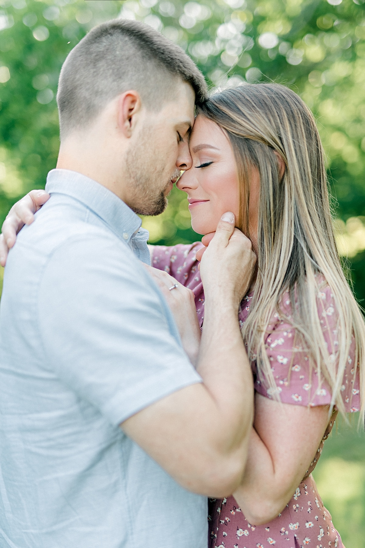 engaged couple sitting standing face to face nose to nose with eyes closed in forest