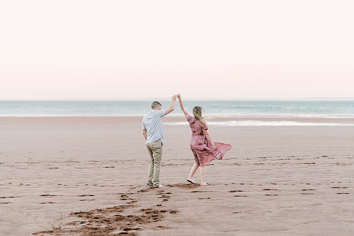 couple dancing by the ocean with pink sky
