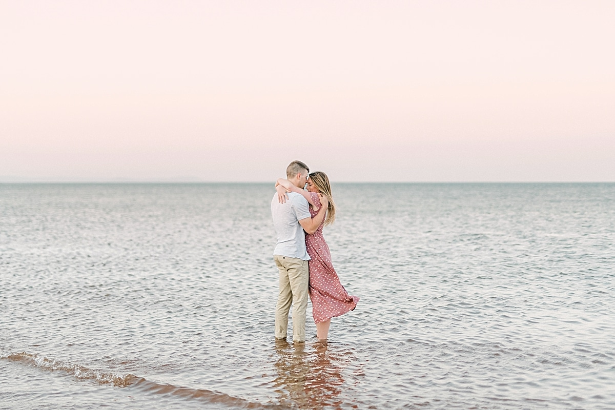 couple kissing in the ocean with pink sky