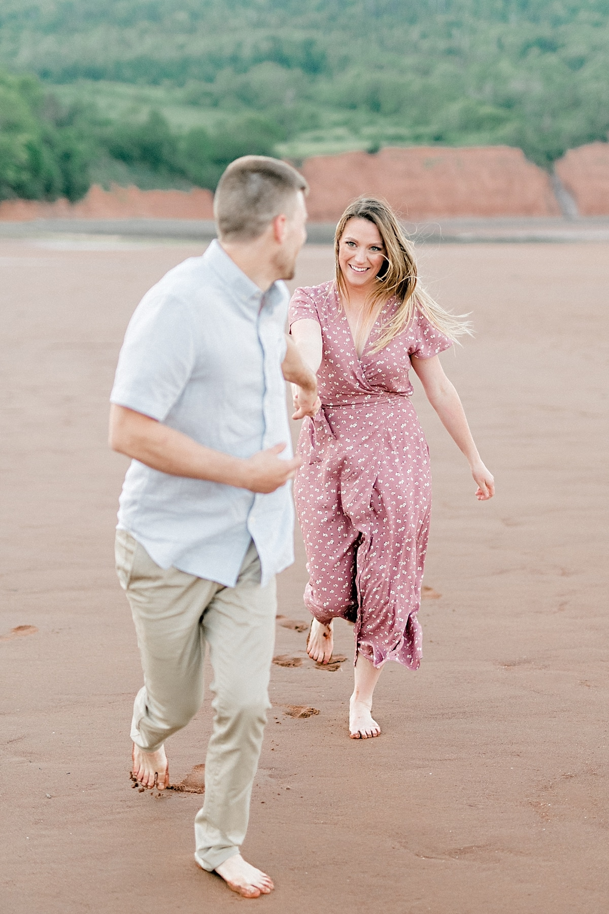 couple running in front of giant tall red cliffs of blomidon beach during and engagement shoot