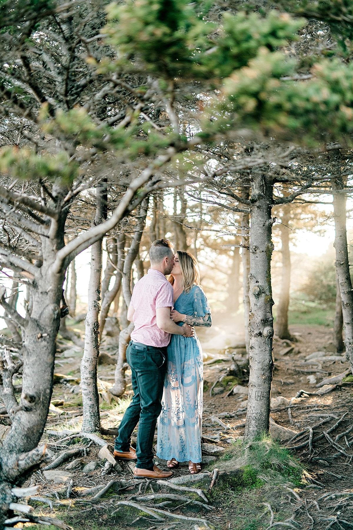 couple kissing in forest with sunbeams and sunshine shining in