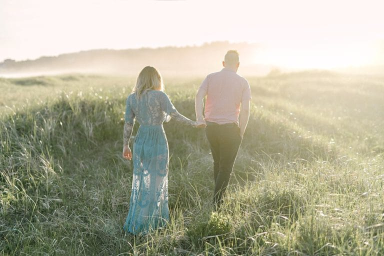 couple walking through hazy golden sunshine shining through dune grass