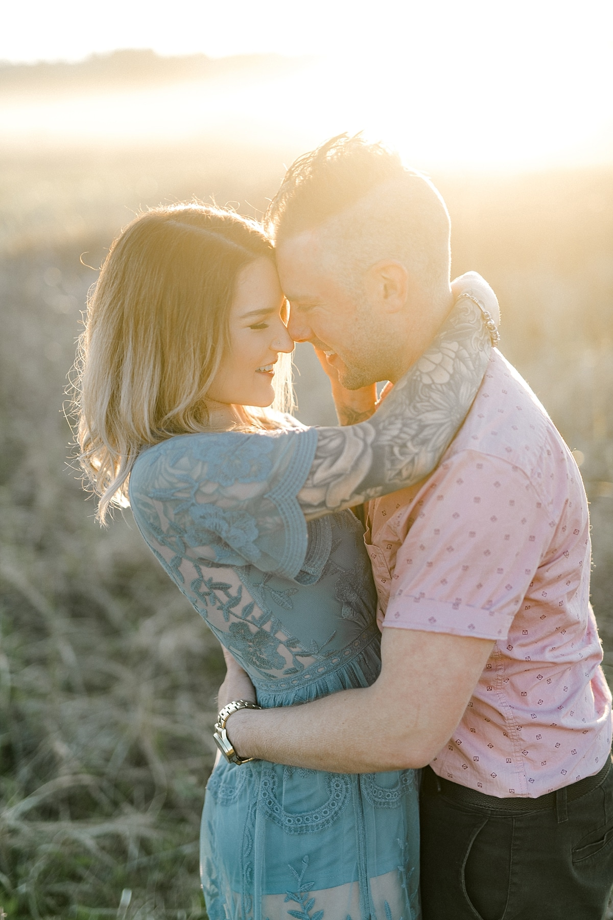 couple hugging nose to nose with golden sunshine causing lens flare behind them