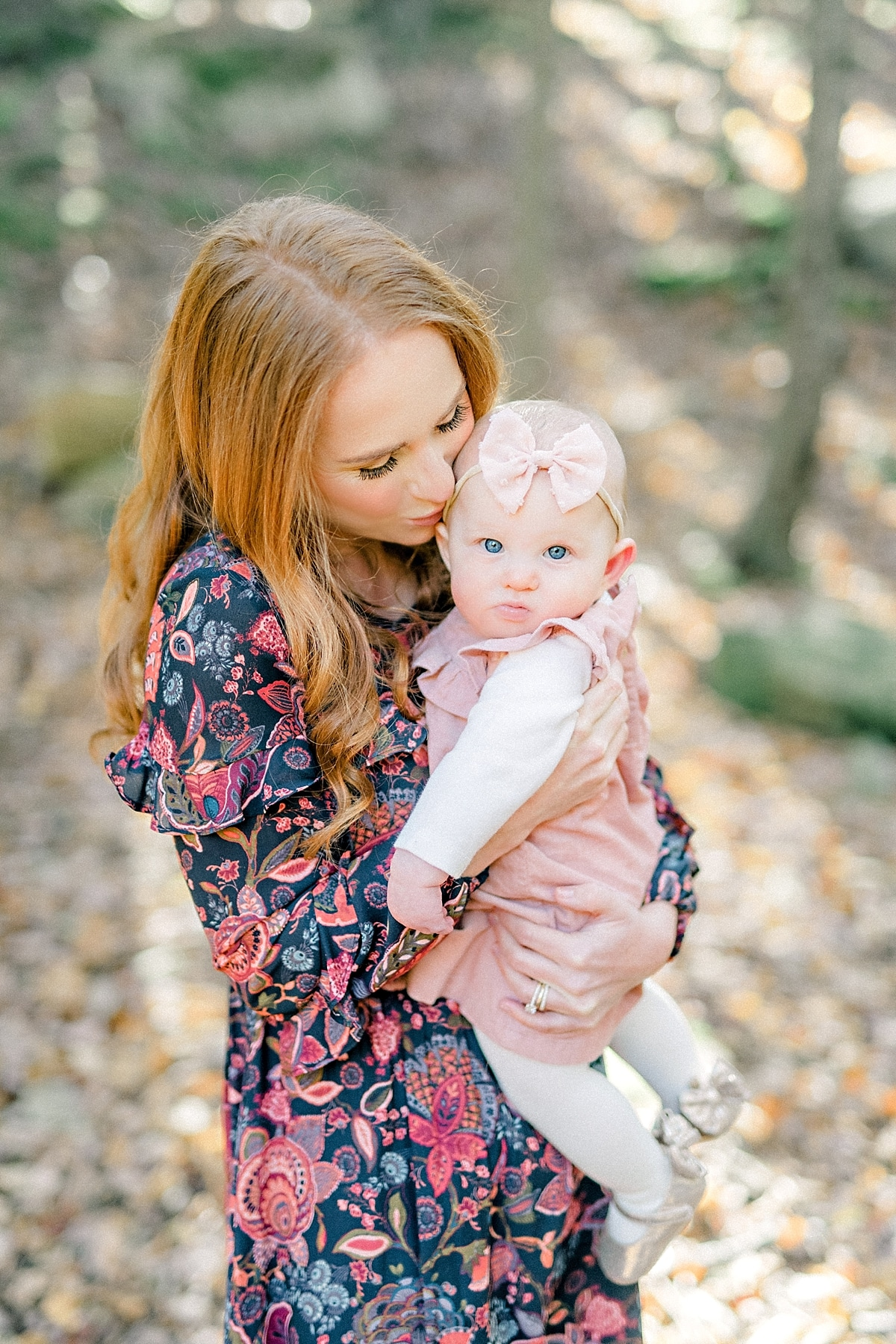 red head mother kisses baby girl on the forhead