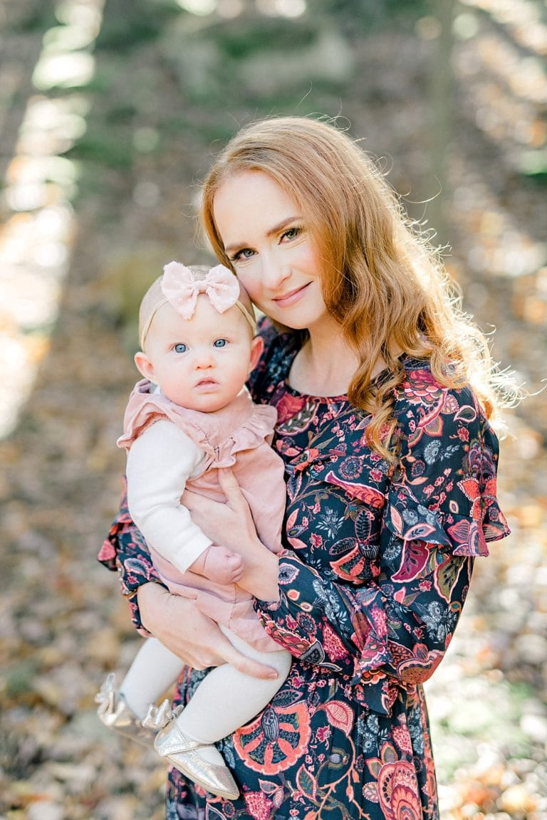 mother with long red hair holds baby girl and smiles during portrait session in the fall time