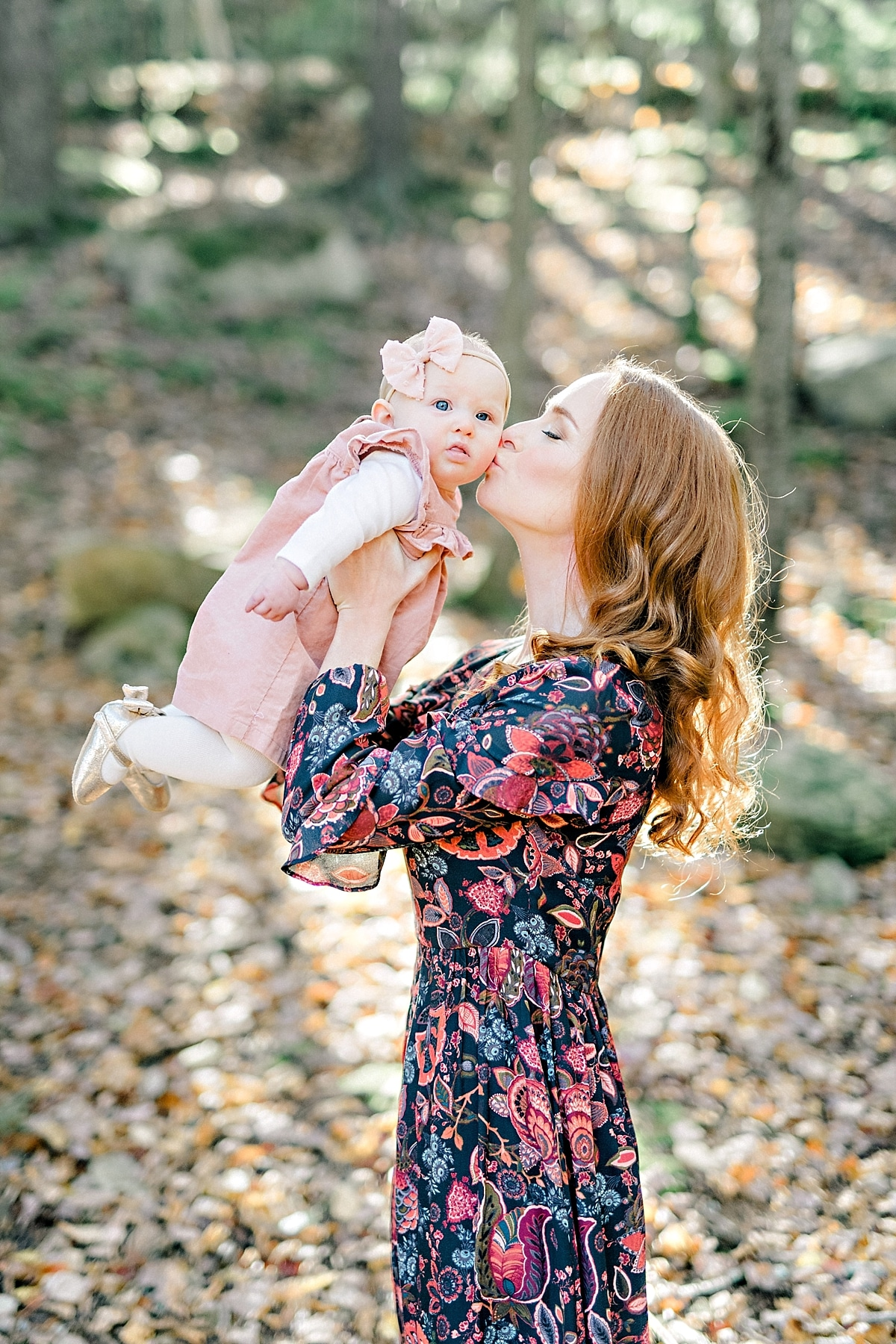 mother with beautiful long red hair lifts baby daughter up for a kiss in the autumn leaves