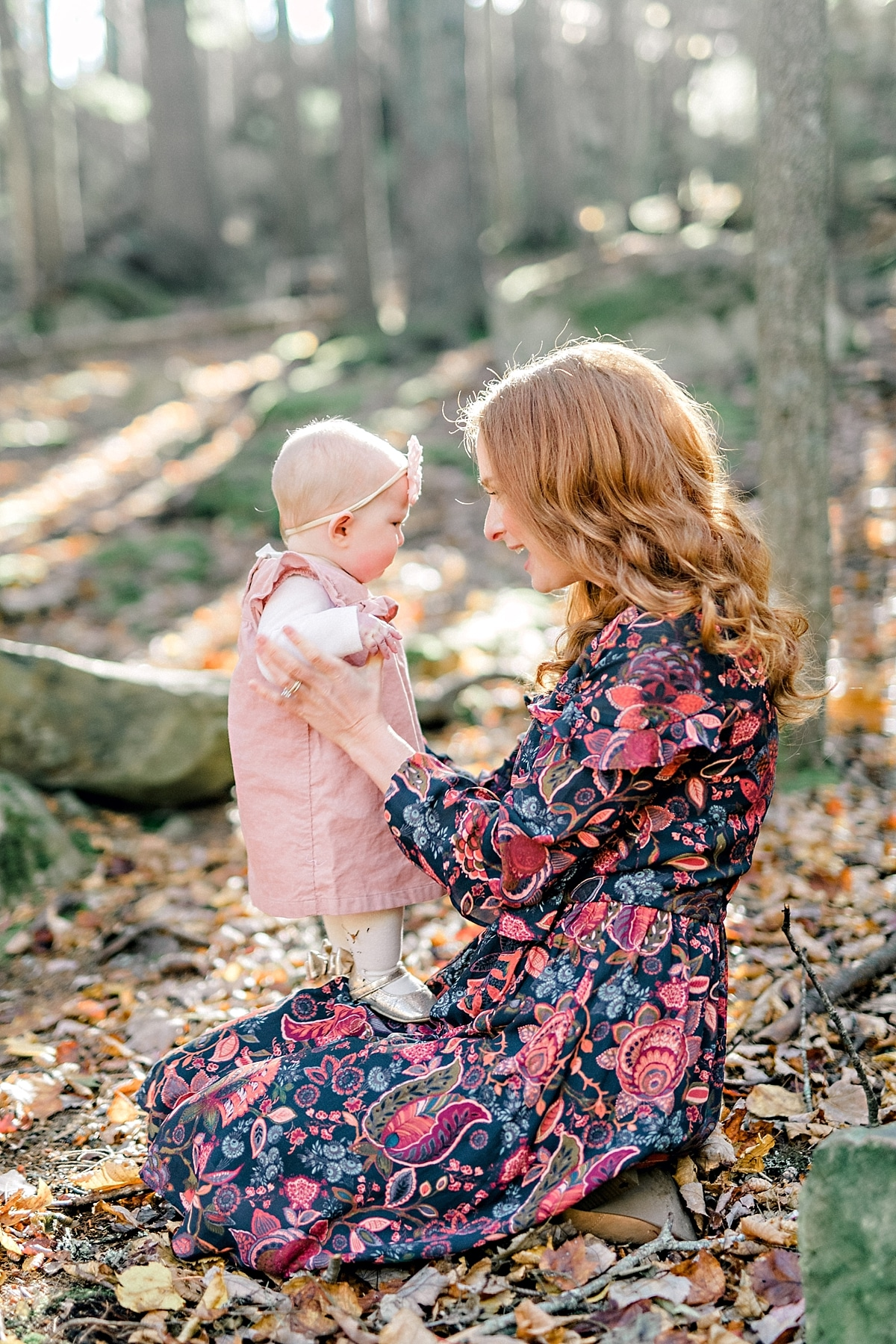 mother sits in fallen leaves during the fall time with baby daughter on he rlap