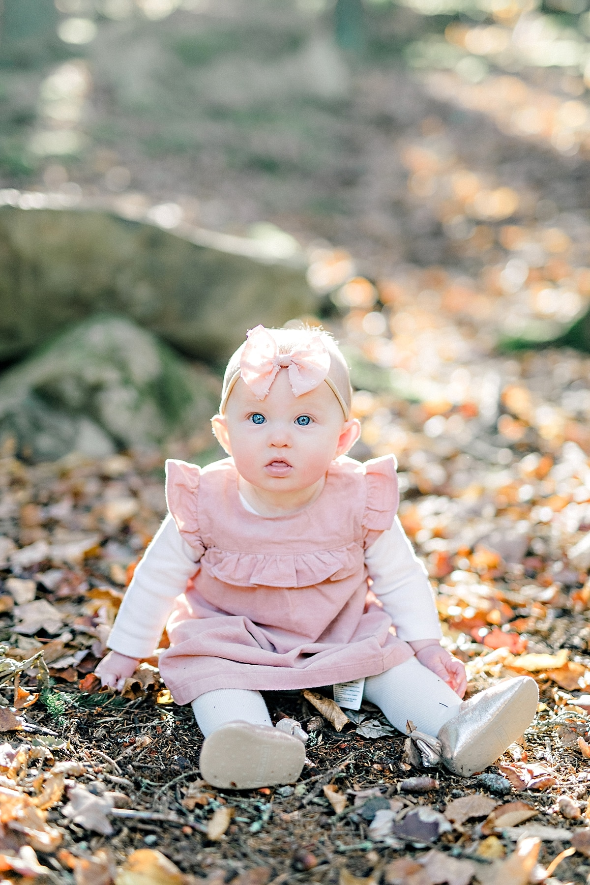 baby girl sits in fallen leaves during autumn portrait session with pink overall dress and pink bow