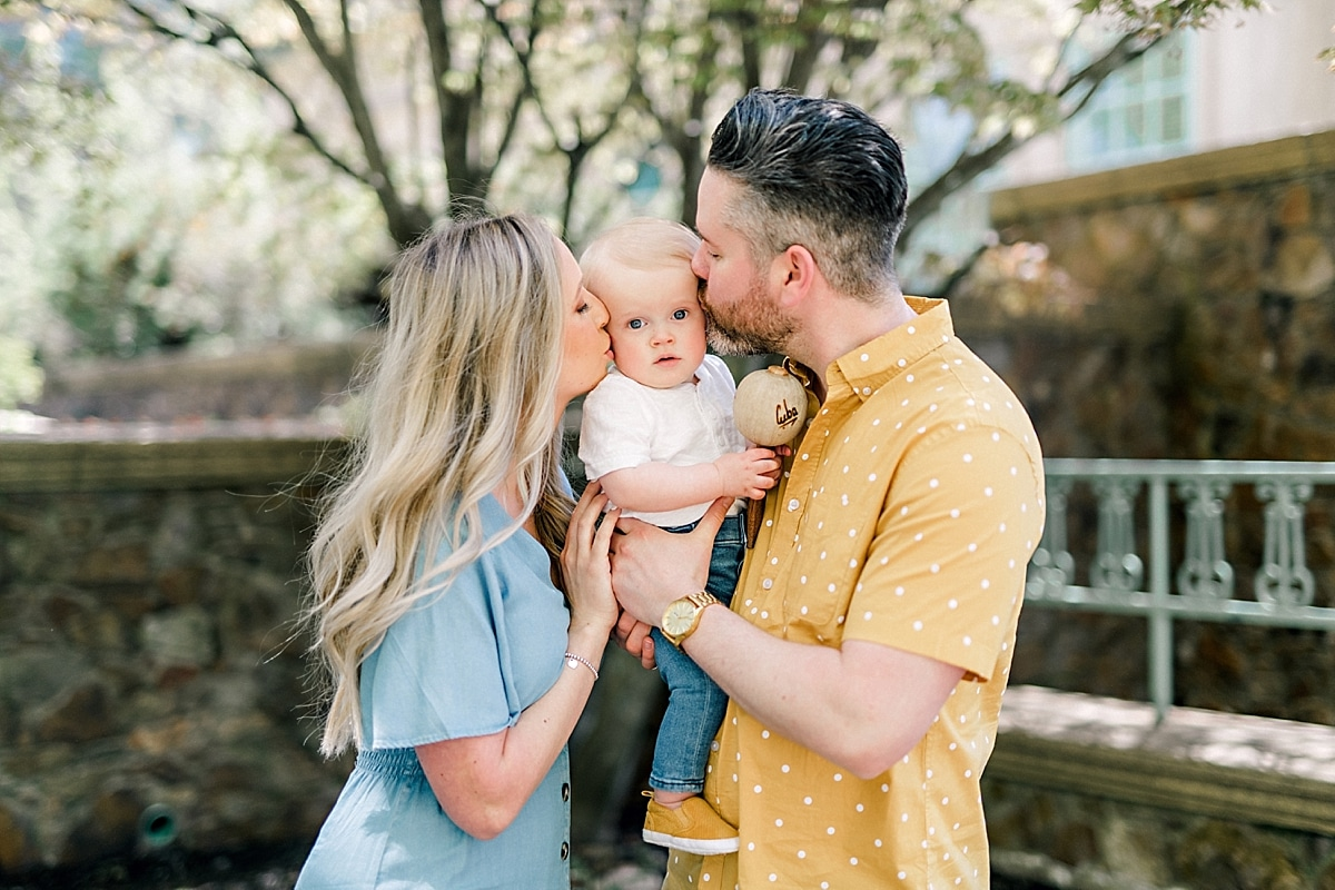 young urban family wearing yellow and blue kissing baby boy in halifax