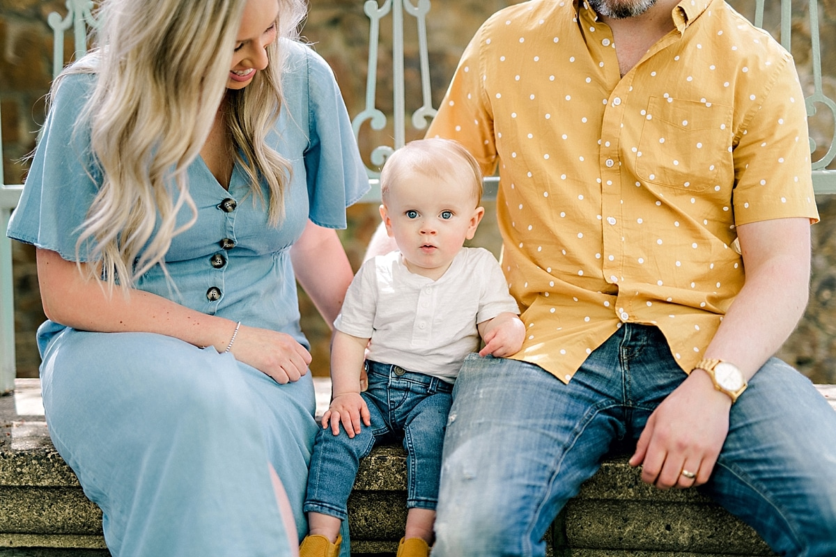 little baby boy sitting between mom and dad during family photoshoot
