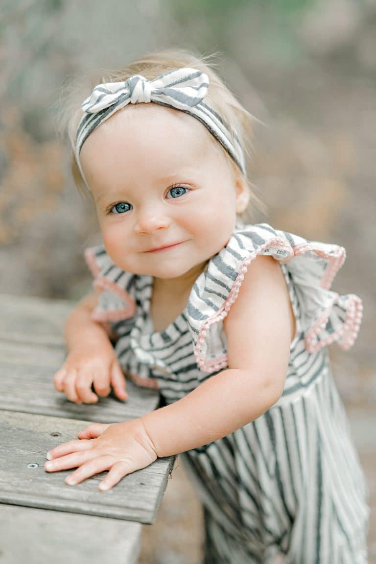one year old baby in ruffled jumpsuit standing and smiling