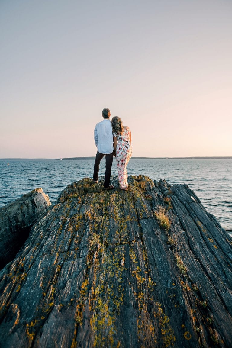 couple standing on top of rocky cliff over the ocean watching the sunset